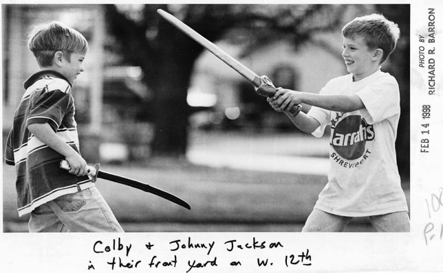Colby Jackson and Johnny Jackson play sword fight in their yard in Ada on Feb. 14, 1998.