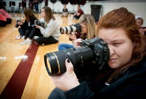 Four photographers with DSLR cameras shoot next to me last night at the Ada Cougar Activity Center.