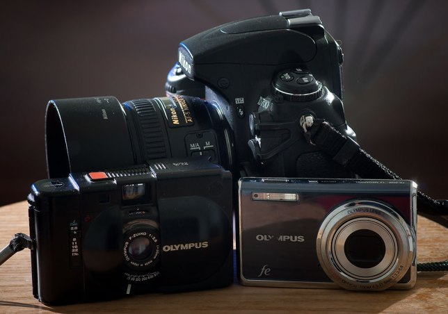 The Olympus XA is pictured with an Olympus FE-5020 and the full-size DSLR, the Nikon D700.