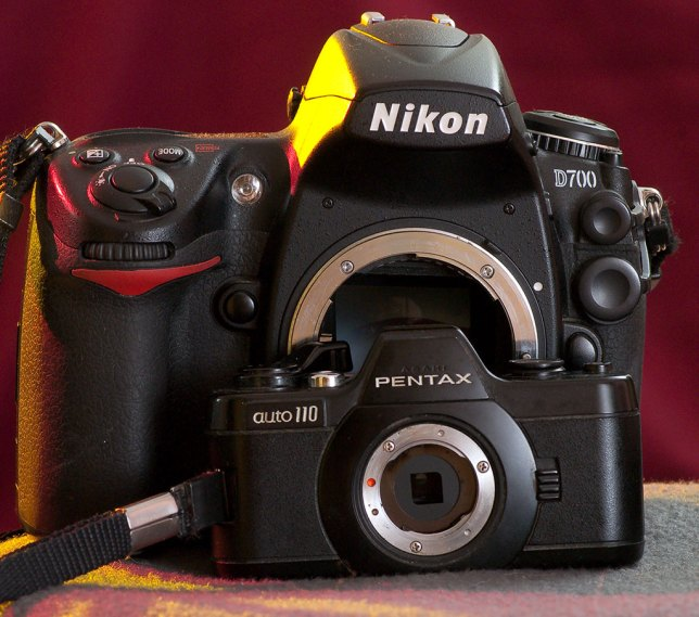 The Pentax Auto 110 sits in front of a full-sized DSLR, the Nikon D700, showing its petite size.