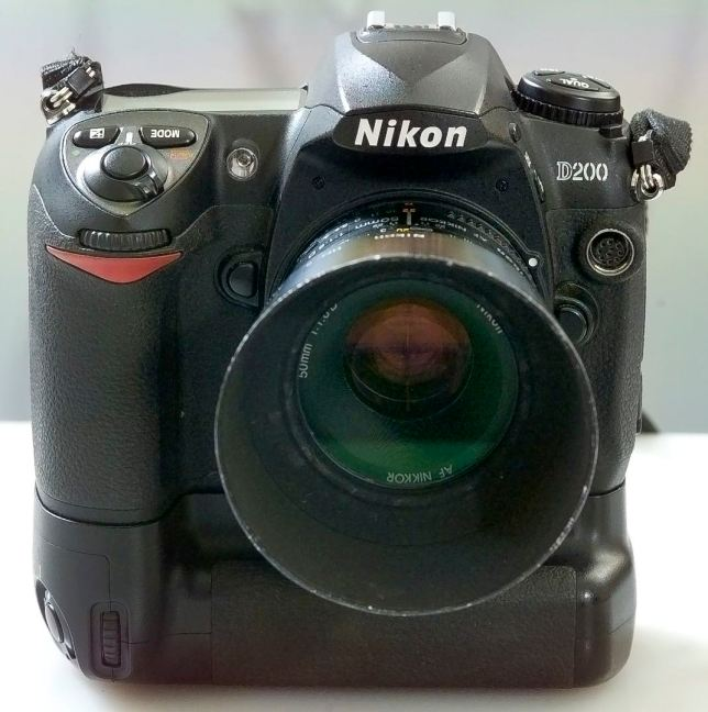 The Nikon D200 digital SLR stands tall on its MB-D200 vertical grip with an older AF Nikkor 50mm f/1.8 lens mounted.