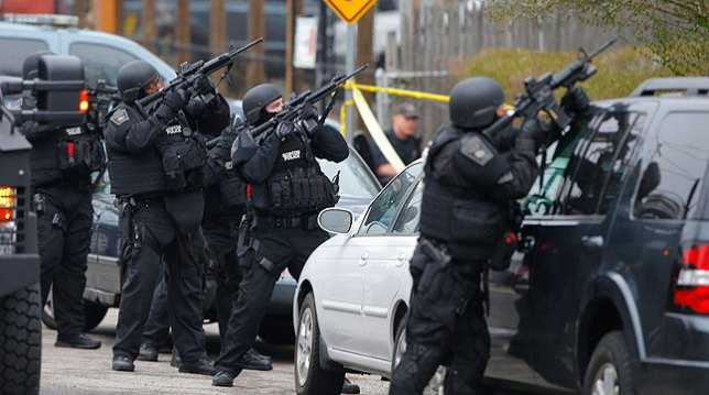 Police officers take position during a search for the Boston Marathon bombing suspects in Watertown, Massachusetts April 19, 2013. It's quite a stretch to look at their weapons and think they are designed for anything other than military and police tactics, and are thus assault rifles.