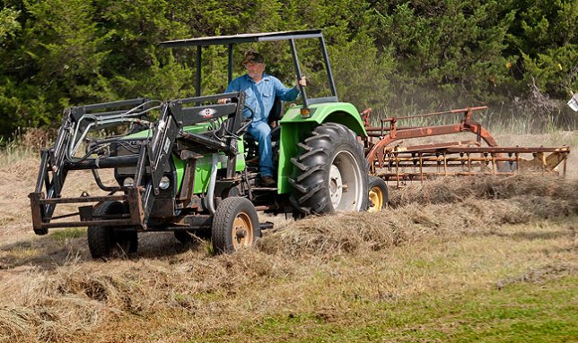Our month-late hay guy chugs along on his tractor as he rakes the pasture he cut in preparation for bailing it.