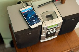 Abby's iPhone plays SiriusXM Radio through her stereo in the living room.