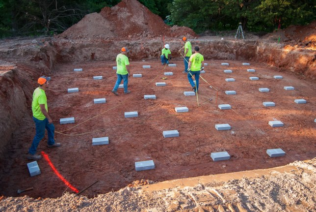 Workers set blocks in the foundation of a cell tower they are installing in the pasture to our north.
