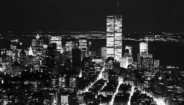 New York City at night, viewed from atop the Empire State Building. The twin towers of the World Trade Center are clearly visible.