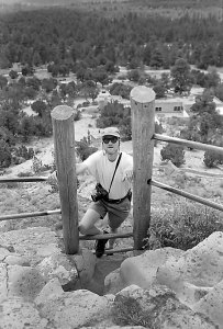 The author climbs a short ladder at Puyé Cliff Dwellings. Note my Fuji 6x7 medium format camera.