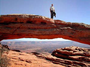 David strolls across Mesa Arch in the Island in the Sky district at Canyonlands.