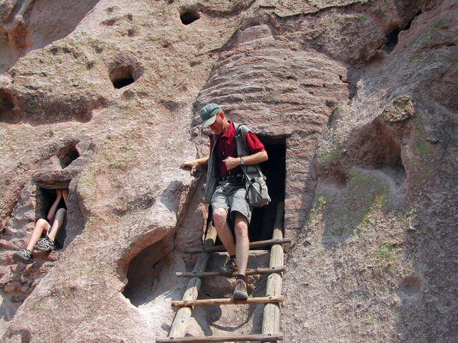 Your host emerges from one of the cliff dwellings open to the public at Bandeiler.