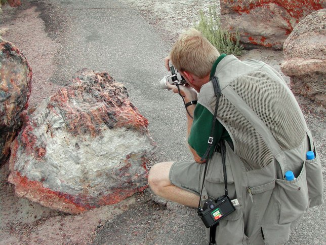 The author photographs petrified wood at Petrified Forest National Park, Arizona. Note my digital camera in hand, and my film camera, with my 16mm fisheye, hanging on my shoulder.