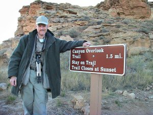 The author poses at the sign for the Canyon Overlook Trail, one of the shorter trails at Chaco Canyon.