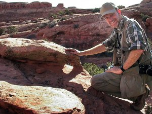 The author poses with a tiny arch on the Devil's Garden trail at Arches National Park.
