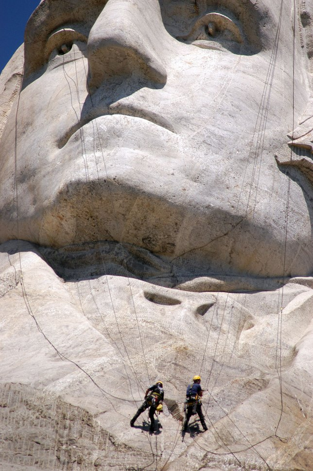 Workers dangle on the faces of Mount Rushmore as they power wash the attraction.