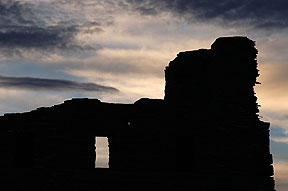 The Abó Ruin is silhouetted against the evening sky.