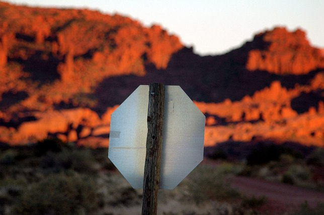 Utah's red rocks stand behind this stop sign at sunset near Castle Valley.