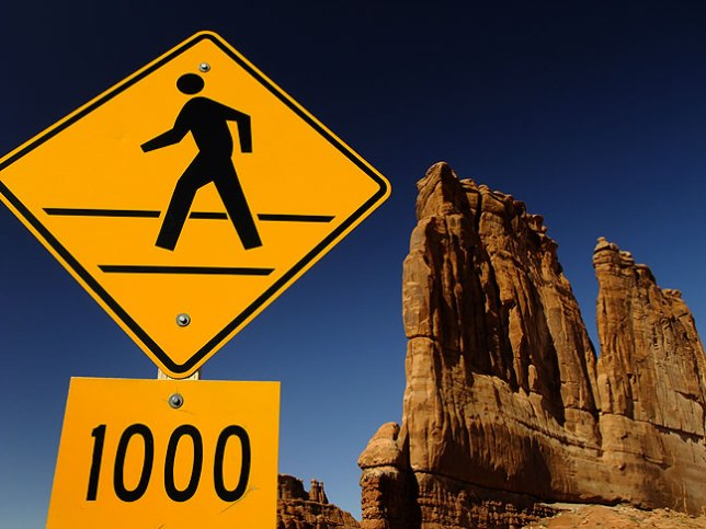 A traffic sign and Courthouse Towers are set against a perfect blue sky at Arches National Park.