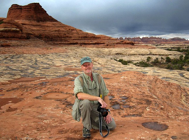 Your host poses on a slickrock bench as storm clouds approach at Canyonlands.