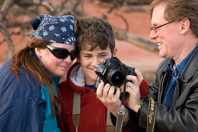 "Deb and David look at the display on Robert's camera in what can only be described as a ""Kodak moment"" while they take turns photographing each other at Grand View Point, Island in the Sky district, Canyonlands National Park."