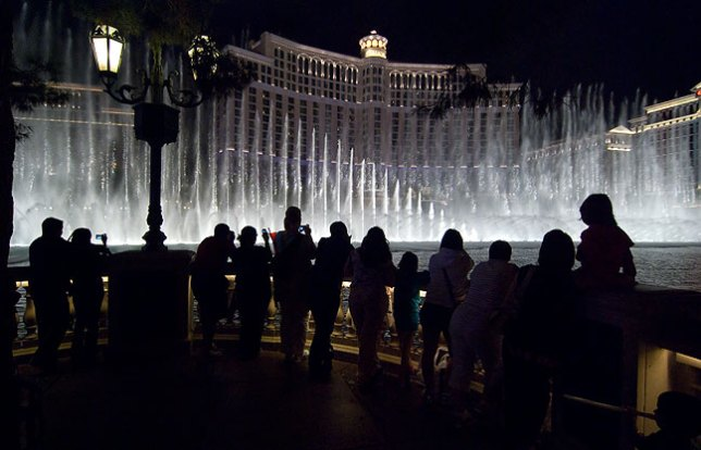 Visitors line the wall around the 11-acre pond to watch a performance of the Bellagio Fountains.