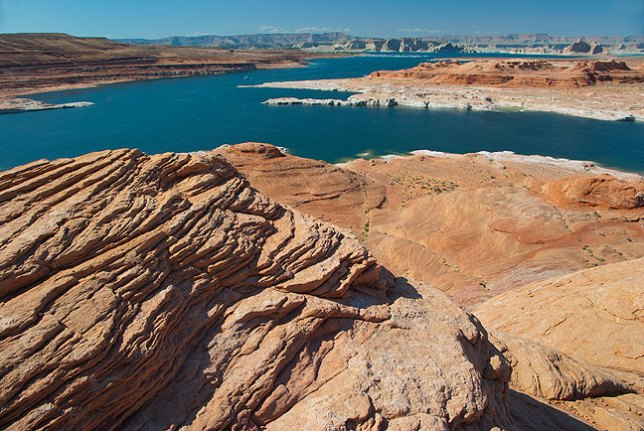 The colors of Lake Powell begin to shine in late afternoon light viewed from a pinnacle north of Glen Canyon Dam.