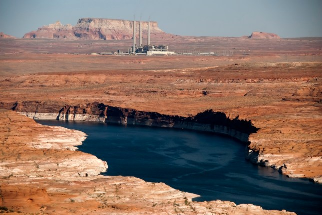 Looking east from Lone Rock, an arm of Lake Powell and the Navajo Generating Station are visible.