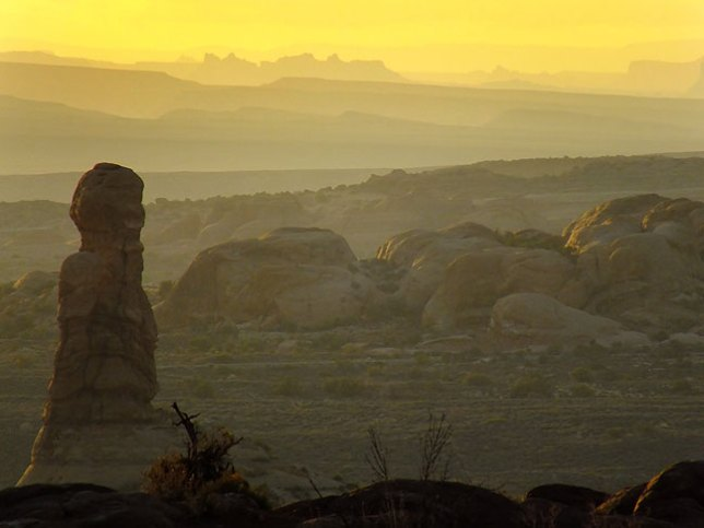 This supertelephoto sunset view looks west across Arches National Park.