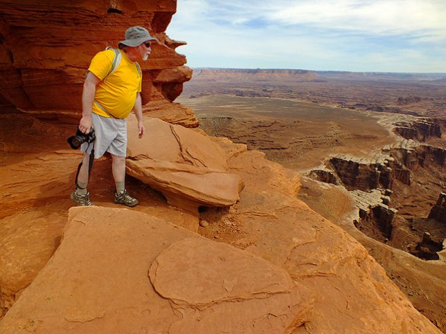 Jim peers warily down a sheer cliff face as we approach the end of the White Rim Overlook trail.