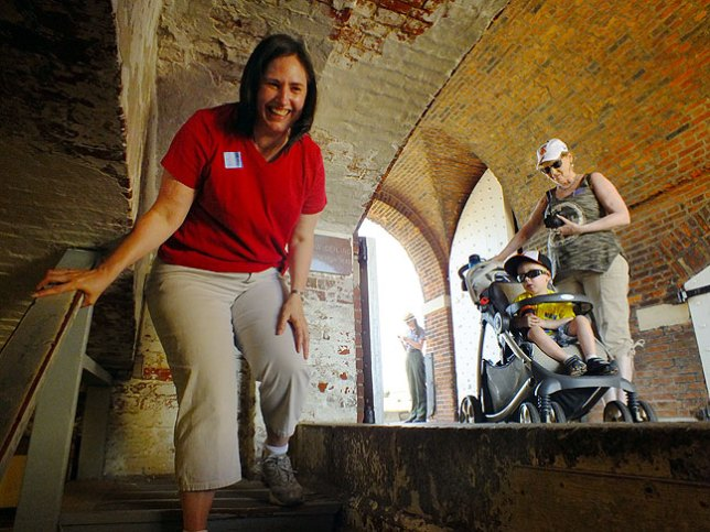 Chele smiles as she steps down into a below-ground area of Fort McHenry. On the right are Abby and Paul.