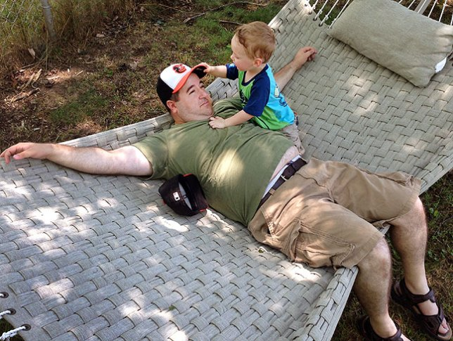 Tom and Pail play on the hammock in their back yard. Tom is a very natural, easy-going dad.