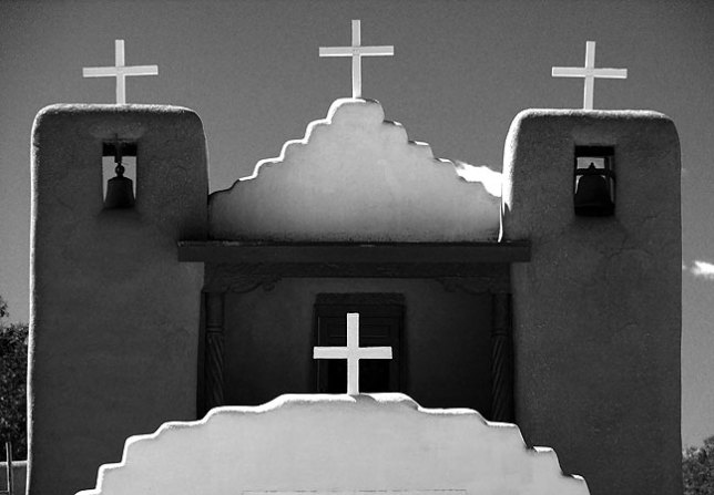 The high desert light of Taos Pueblo creates a scene of striking contrast, like these crosses on the church set against a clear sky.