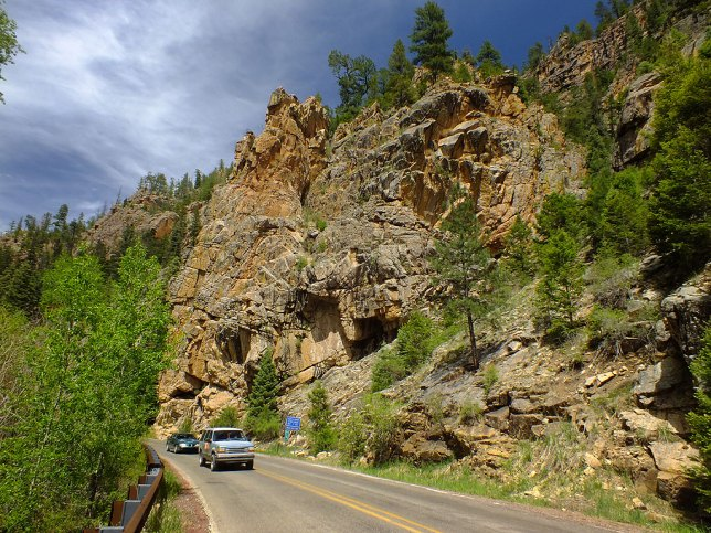 Highway 63 passes several handsome palisades, like this one, with traffic passing to show scale.
