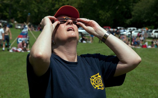 Nicole uses her eclipse glasses to watch as the crescent sun becomes a sliver.