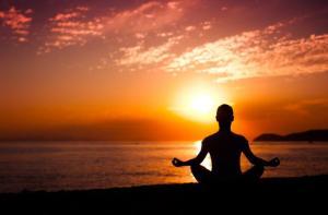 Person meditating on beach at sunrise.