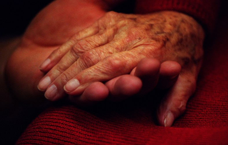 The hand of Violet Wightman, 97-yrs.-old, is cradled in the hand of classmate Richard Sandner as he reads her writings out loud during class at Fullerton College in Fullerton.