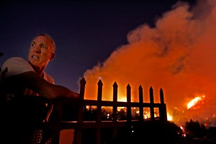Allan Kolins keeps an weary eye on the brushfire from his home on Glendower Ave. near Griffith Park in Los Angeles Tuesday May 08, 2007. The fire behind him is near the Greek Theatre.