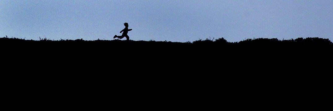 A boy is silhouetted against the late-afternoon sky as he romps along the hills that overlook the Pierce College campus in Woodland Hills, Ca.