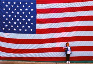 Five-year-old Savannah Avila (cq) of Carson waves a flag and is backed by another, bigger flag as she has her picture taken during a Veteran's Day Celebration at Veteran's Park, Sunday morning in Carson.