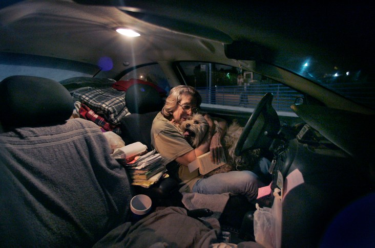 After a night of t.v. and reading in her car, and before turning in for the night, Lee Sevilla shares a tender hug with her dog Sandy in the parking lot at a Rite Aid store, late Friday night in El Segundo, May 05, 2006. The 71-year old homeless woman has lived in her car with Sandy for 8 years. *Note - they do not sleep in the store parking lot.