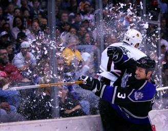 Ice goes flying as King Aaron Miller, right, slams Chicago Blackhawk Rene Bourque into the glass during second period at the Staples Center, Saturday in Los Angeles. - 02/11/06