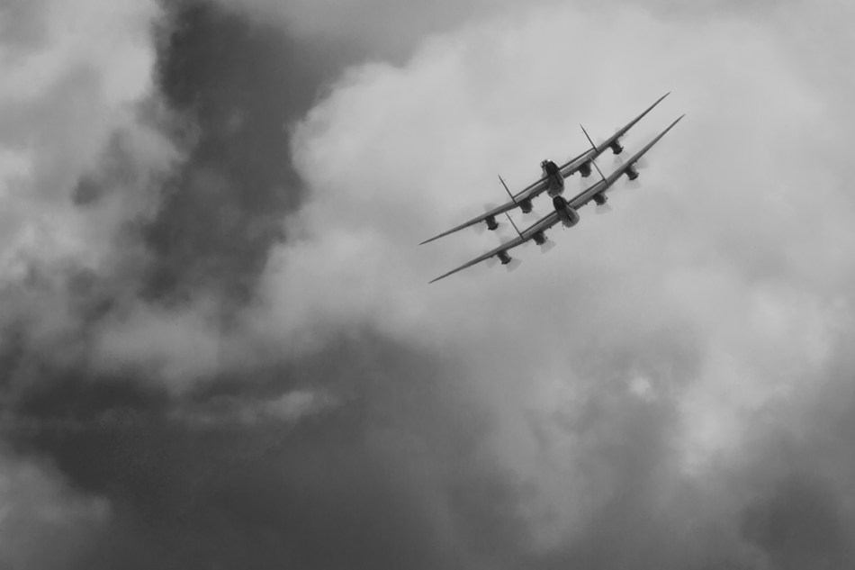 "Black and white photograph of the CWHM Lancaster ""VeRA"" and the BBMF Lancaster ""Thumper"" flying off"