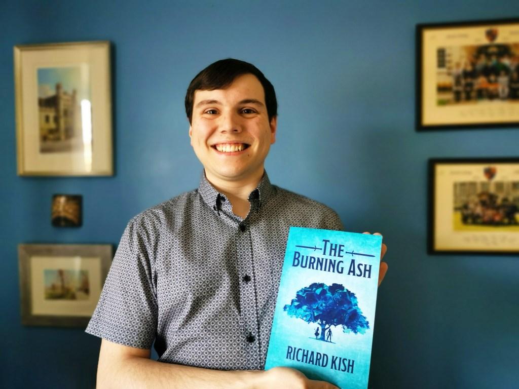 Richard Kish holding his debut novel, The Burning Ash
