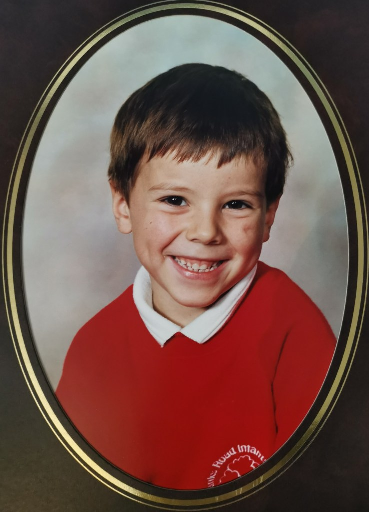 A very young smiling Richard in a red jumper