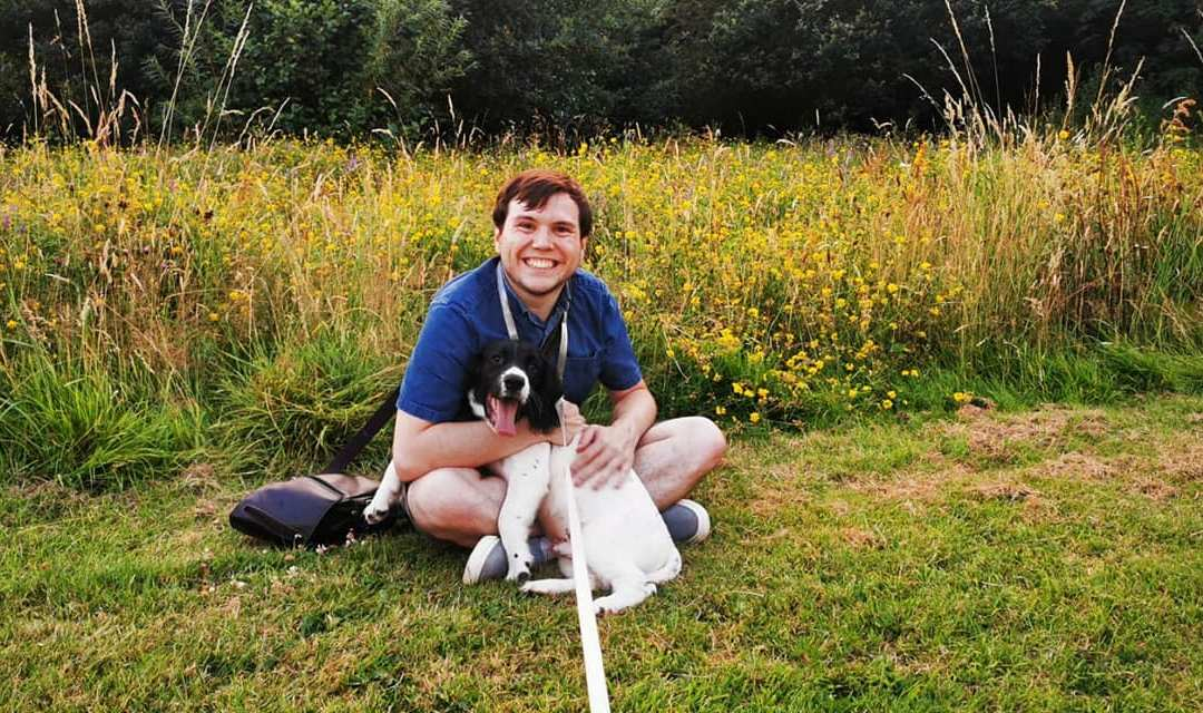 Richard and black and white springer spaniel puppy Milo in front of a wildflower meadow