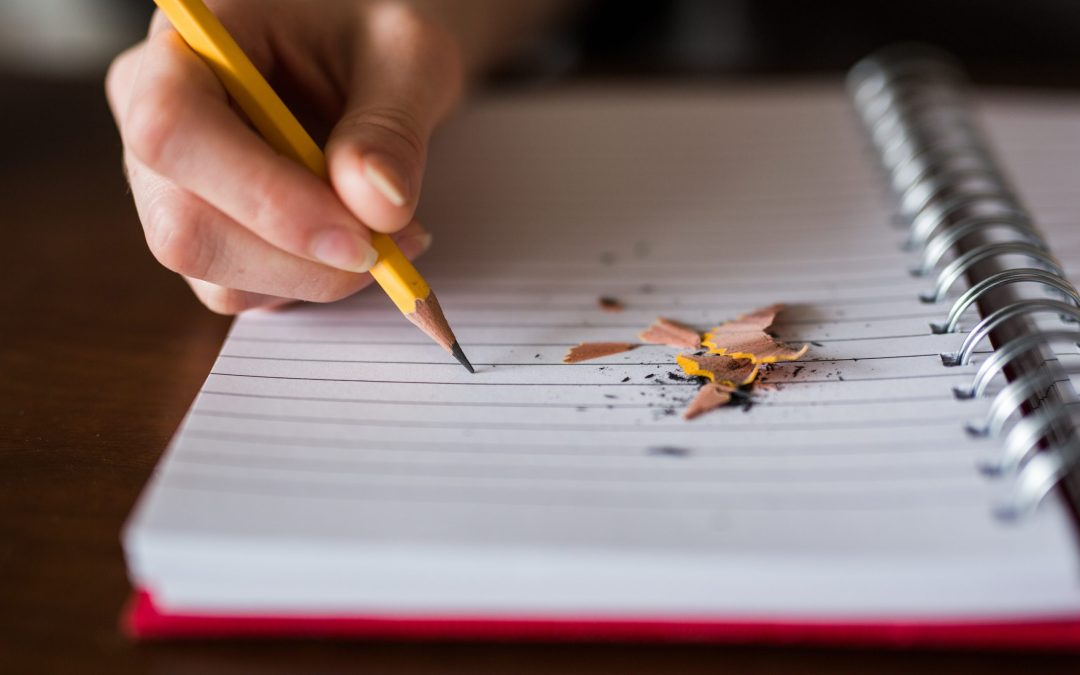 Person holding a pencil writing in a notebook with some pencil shavings scattered on top