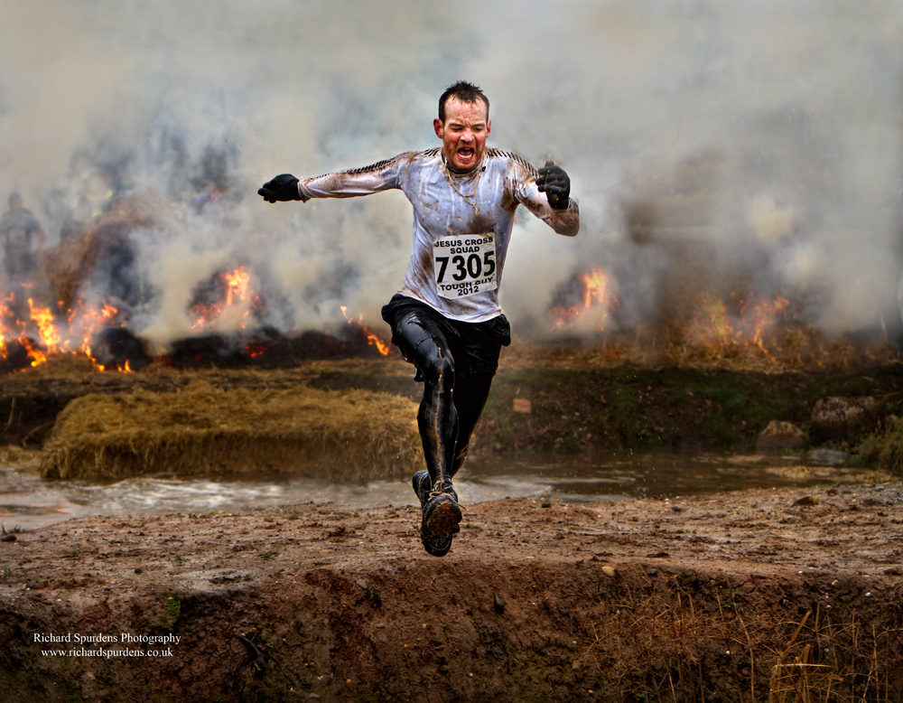 colour image of a tough guy competitior runing across the water trap with lots of smoke in the background