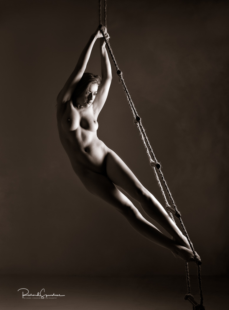 artistic nude image of model rosa brighid using a rope ladder to hang and make a curved figure shape