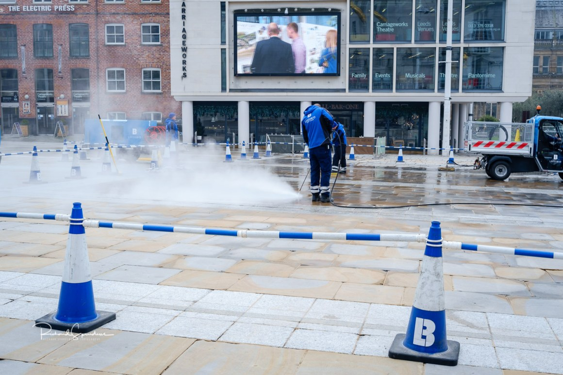 image showing the leeds bid team using a steam cleaner of the paving stones in the millennium square (april images)