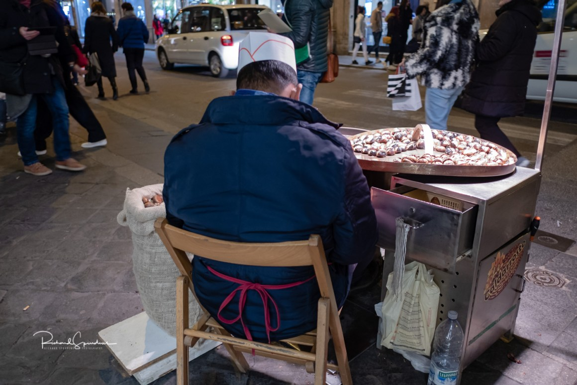 Image showing a small food stall with the vendor looking at his phone shot from behind (photographing rome at night