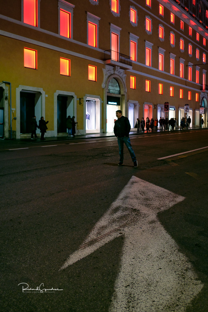 image showing a large road lane direction arrow pointing to figure looking down the road against a large build where all the windows have an orange glow coming from them (photographing rome at night)