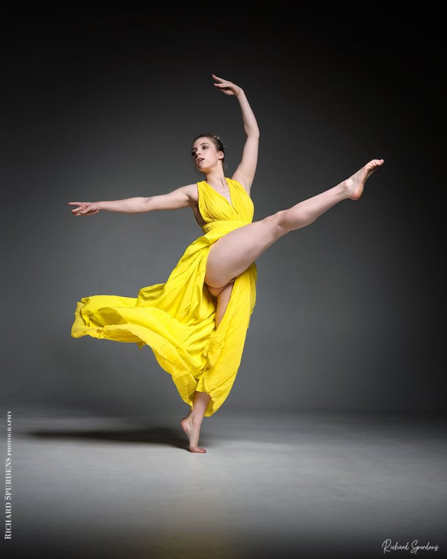 Dance Photographer - Dance photography - colour dance image of dancer ariel taylor wearing a yellow dress and reaching up with dynamic dance moves with a straight high kick leg